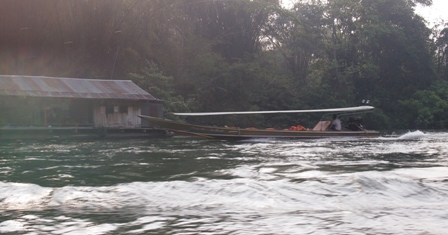 Long tail boat at dawn on river Kwai