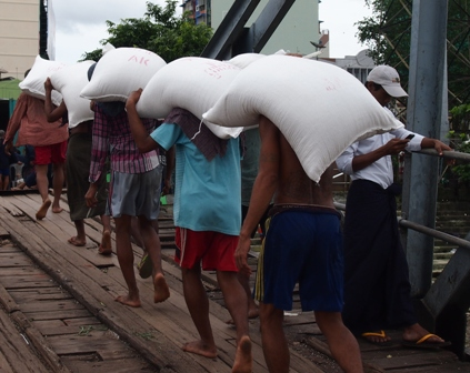 Hard work under rice sacks at Yangon wharves
