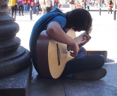 Young guitarist practicing outside Teatro Degollado